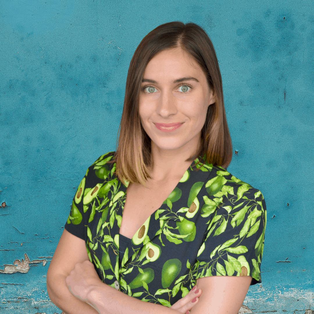 Sarah Muncaster in an avocado dress in front of a blue background