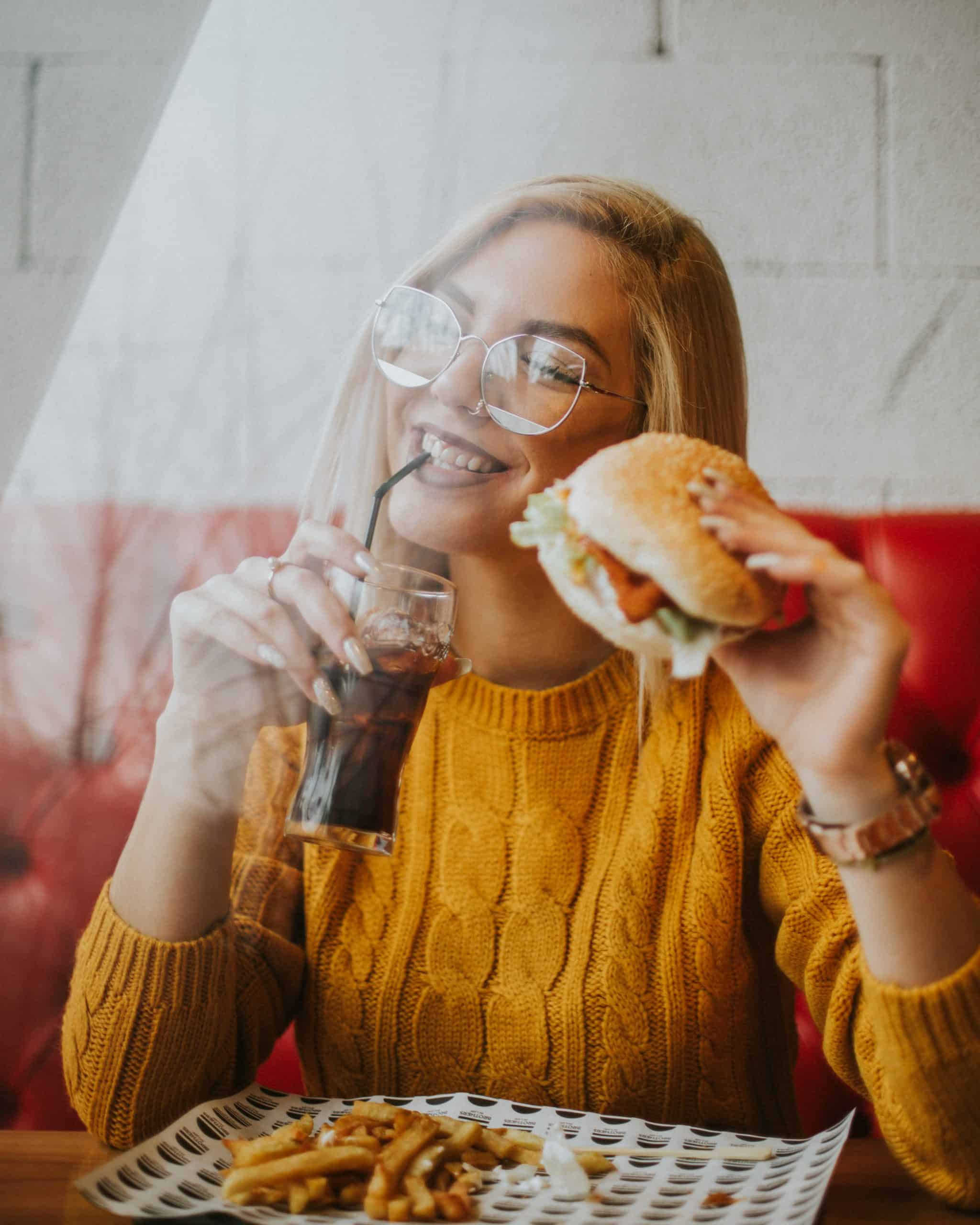 Woman eating burger and coke practicing positive food language