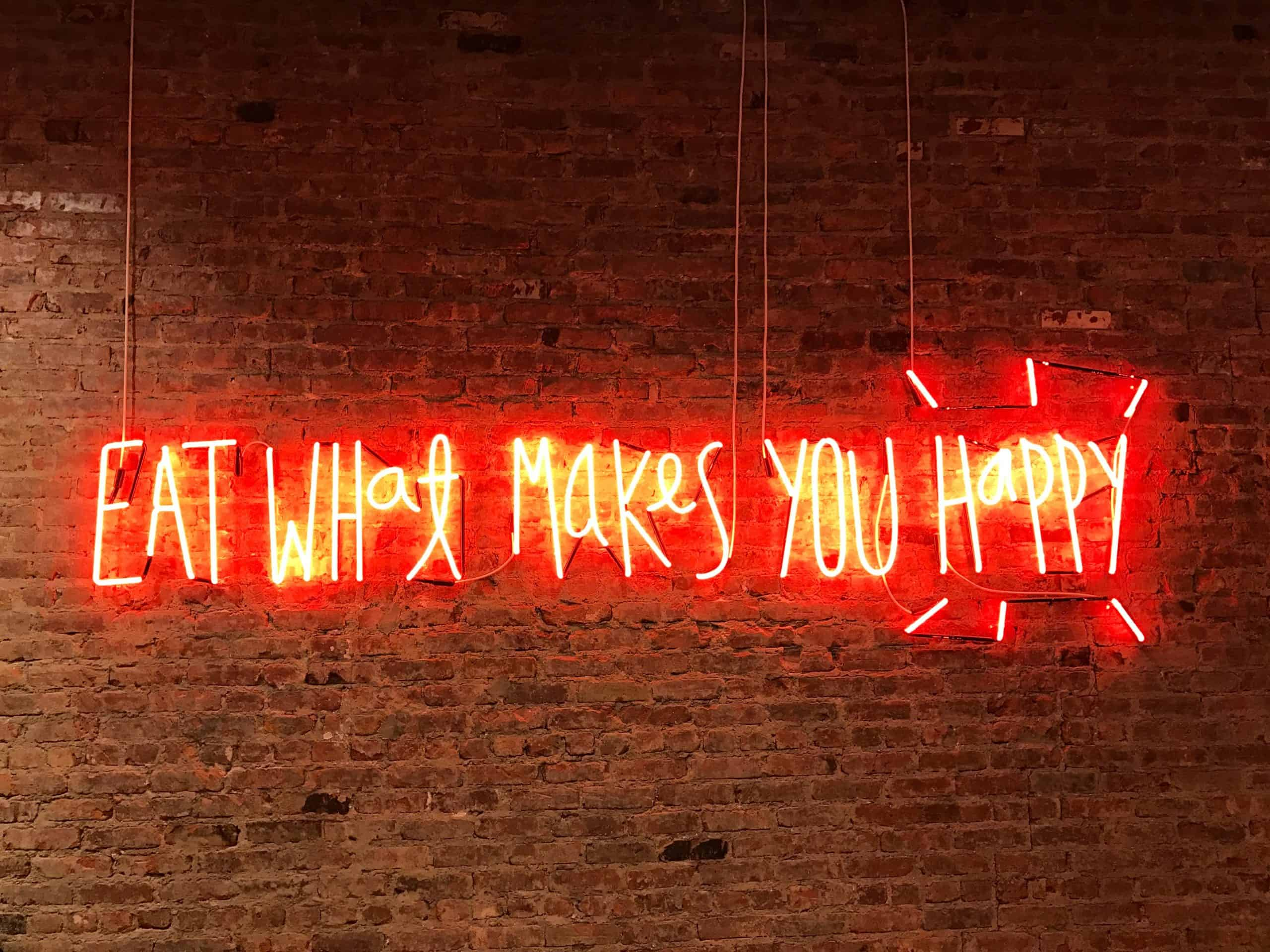 Neon sign over brick wall show positive food language