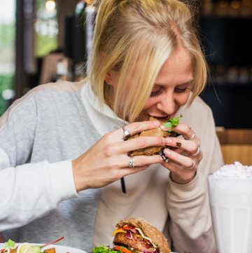 a blonde woman happily eating a burger
