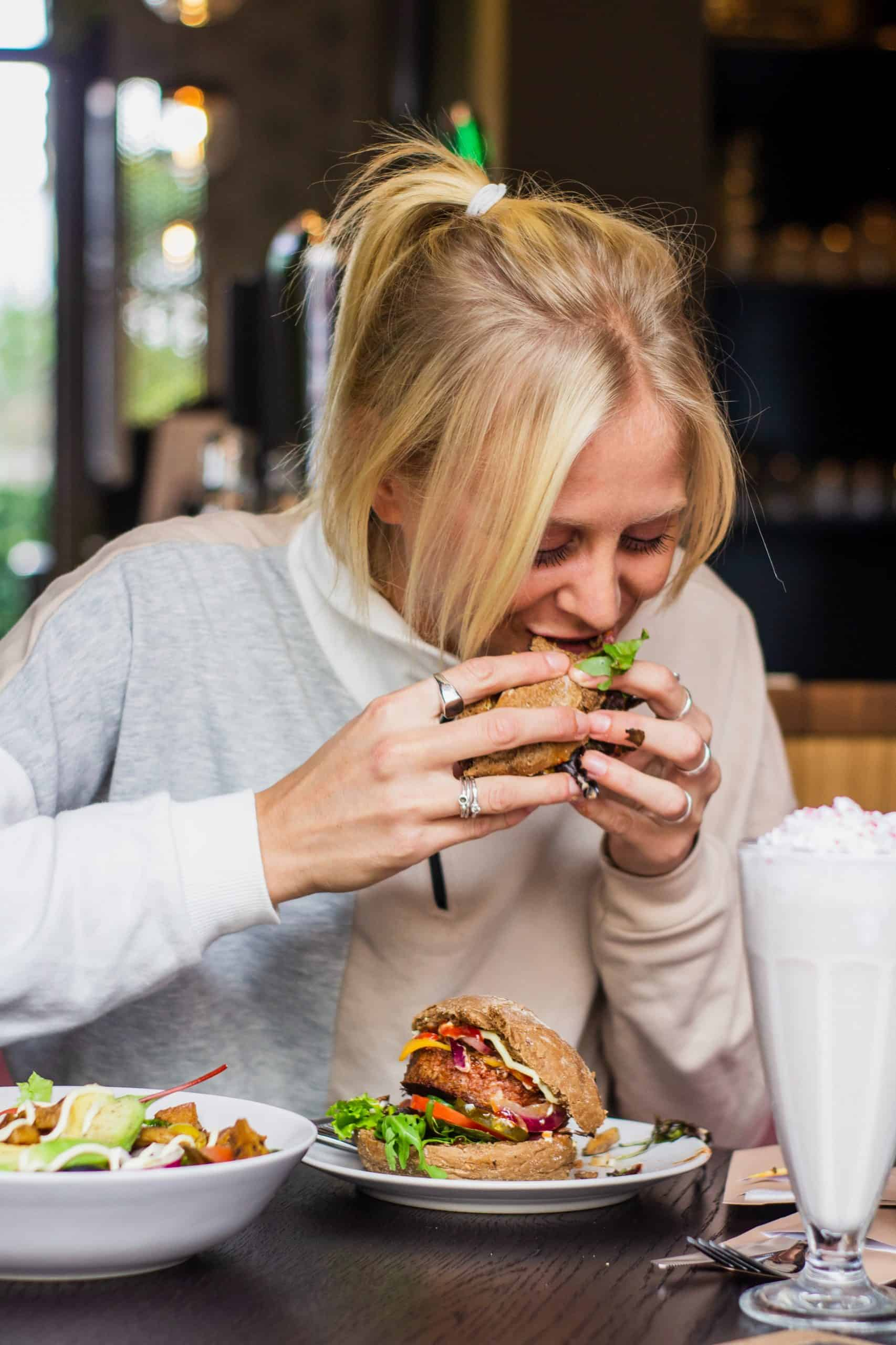 blonde woman eating a burger and not being affected by negative food language